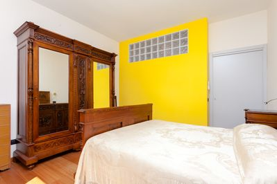 Double bedroom with wardrobe made of typical Sorrento woodworks.