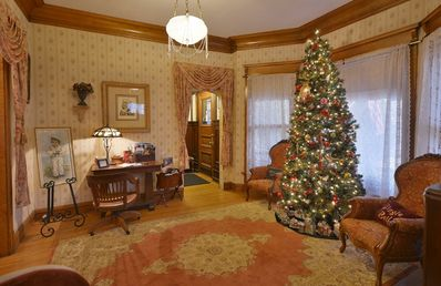 A Victorian Christmas. A room full friends and family gathered around the tree.