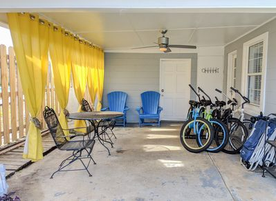 Carport set up as an outdoor patio. 4 adult bikes + backpack style beach chairs
