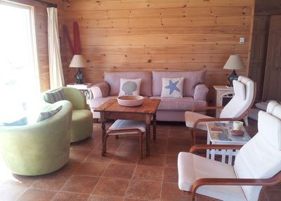 Sun-filled living room with a big comfy couch, and swivel chairs so you do not