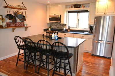 Remodeled kitchen with granite counters and hickory wood floors