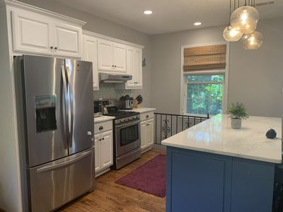 Stove, fridge, microwave, instant pot, island on one side of kitchen
