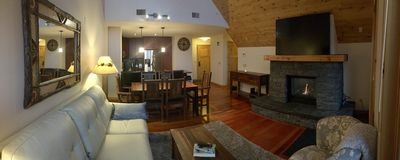 "Relax in an open kitchen/dining/living area with fireplace and 65"" Smart TV"