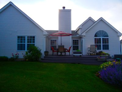 This is a view of the back of the house with the deck and gardens and gardens.