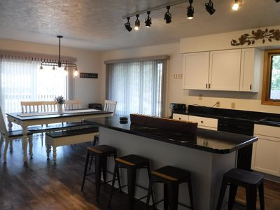 Spacious kitchen area with a sliding glass door leading to a huge deck