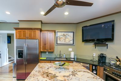 Granite island and large screen tv in common area.