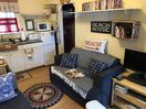 Comfy couch with hardwood floors and large dvd collection,