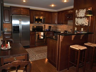 Full kitchen with stainless appliances, granite countertops and tile backsplash