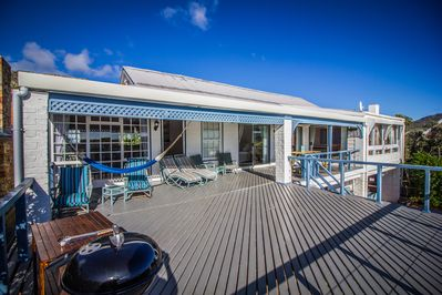The sundeck featuring loads of outdoor furniture and weber barbecue