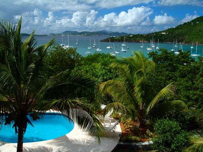 Pool area surrounded by lush tropical gardens, boats swaying, St. Thomas Views