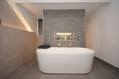 Designer suite large bath and separate walk in shower behind feature wall
