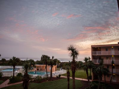 Beautiful sunset casts its rays on sky outside our window! Note view and pools!