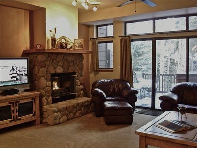 Living room with river rock gas fireplace, plasma TV, and entertainment center