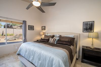Master bedroom has a king bed and view of the backyard