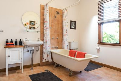 Bathroom with deep claw foot bath and overhead shower