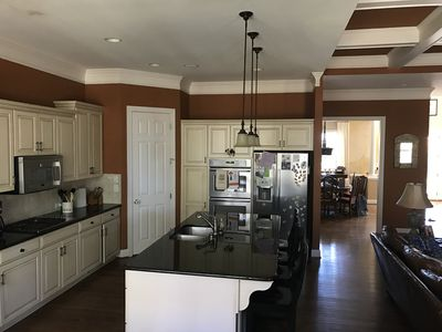 Kitchen that looks into the den and dining area
