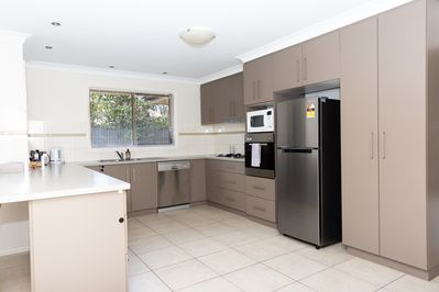 Large modern kitchen with stainless steel appliances - includes: fridge, microwa