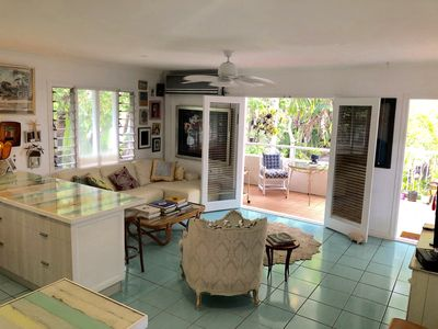 The living room opens to the verandah, with daybed, dining table and bbq