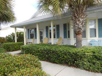 Sundial Cottage front porch complete with rockers, palm trees, and flowers!