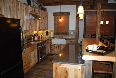 Custom kitchen with granite counters, farmhouse sink, and hand made log bar.