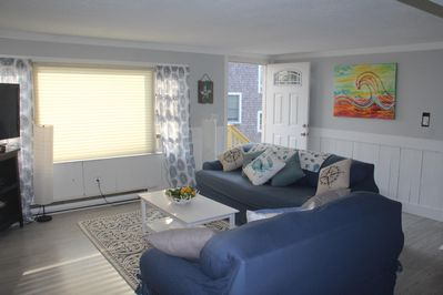 The upper living room has a bright, sunny window and a small front porch.