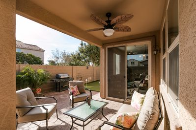 Beautiful outdoor patio area with a putting green, BBQ, Seating, & lounger chair