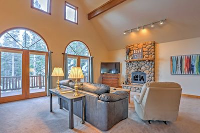 The living room features cathedral ceilings and a wood-burning fireplace.