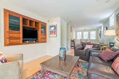 Cozy yet spacious living area with large flat-screen TV, leather furnishings