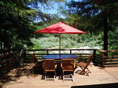 Sunny deck over looking the Russian River with a Kayak in the water.