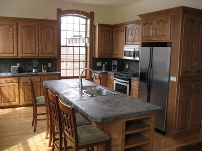 Custom kitchen features stainless steel appliances and beautiful tilework