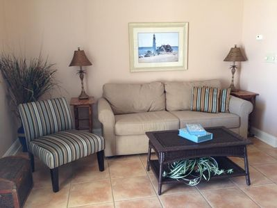 Living room, wall of windows/door to patio, direct ocean view, black out drapes