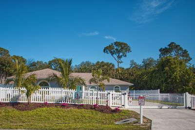 Tropical landscaping with a variety of palms, including splashes of color, making the yard delightful! Completely fenced perimeter with electric gate. This home sitting across from a preserve, that has kayaking swimming and fishing.