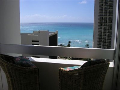 This spacious balcony has a great ocean view with furniture for outdoor dining.