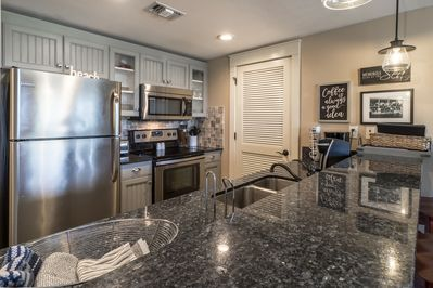 Kitchen w/SS appliances and granite countertop.  Vented door is laundry room.