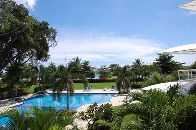 210 Palm Beach balcony view over the pool and gardens to the beach & sea beyond.