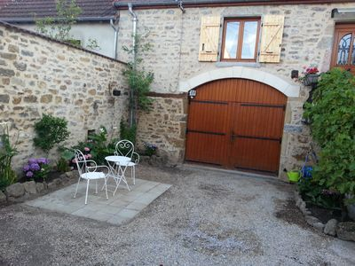 South-facing courtyard and garage entrance with a garden behind