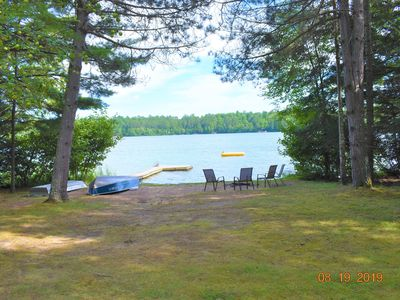 Photo for Northwoods getaway with serene setting of level lake frontage and campfire area.