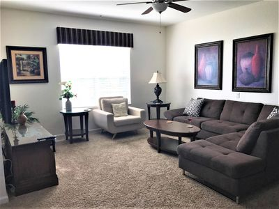 """Relax in the spacious Living Room with large sectional, comfy chair, & 50"""" HDTV"""