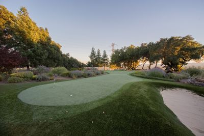 Five hole putting green with sand trap