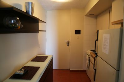 A kitchen equipped with a stove, microwave, plates, cups utensils, and a fridge.