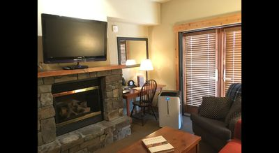 Living area with flat screen TV, gas fireplace, summer seasonal portable AC unit and desk area