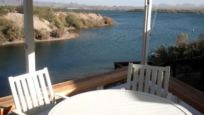 Waterfront deck with ample seating, awning, and mister system