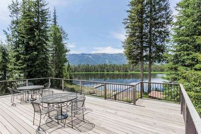 Wooden balcony with patio table and chairs overlooking blue lake and mountain