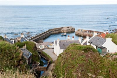 A view of Pennan from the clifftop road.The Harbour House is in centre of image.