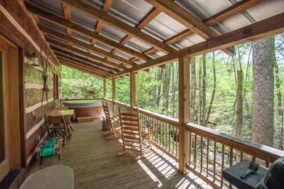 Grill, rocking chairs, hot tub and table for two overlooking the creek