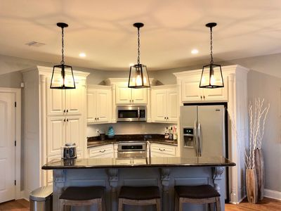 The open kitchen has all new stainless steel appliances w/ bar stools for three.
