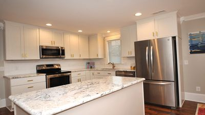 Open kitchen laid out perfect with a food prep and service bar.
