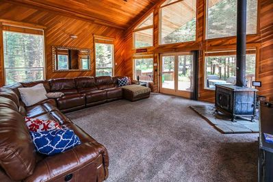 Large brown leather sectional in front of a wood stove and balcony doors