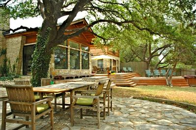 Large Deck/Seating area to the rear of the home. Large Tree Covered Stone Patio