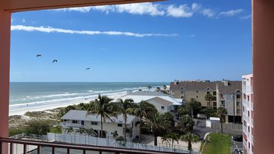 Top floor view of sky, beach,  ocean, and birds  from condo balcony